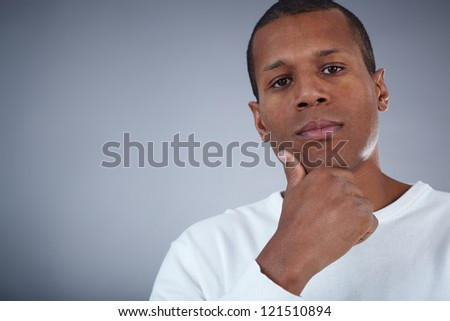 Image of young African man looking at camera with pensive expression - stock photo