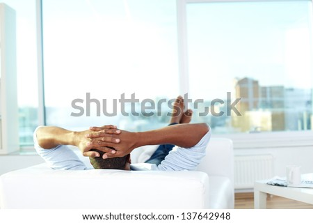Image of young African man lying on sofa and having rest - stock photo