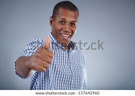 Image of young African man showing thumb up and looking at camera with smile - stock photo