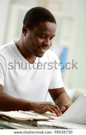 Image of young African man typing on laptop at home - stock photo