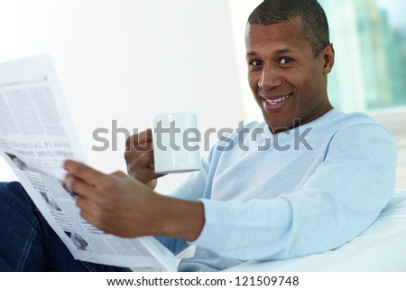 Image of young African man with cup and newspaper looking at camera - stock photo
