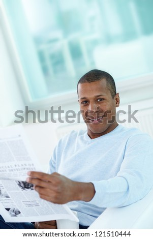 Image of young African man with newspaper looking at camera - stock photo