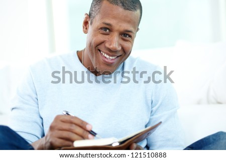 Image of young African man writing something in notepad - stock photo