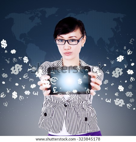 Image of young asian woman showing digital tablet screen with currency symbols flying away. Making money online concept - stock photo