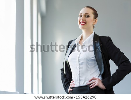 Image of young attractive businesswoman in business suit smiling