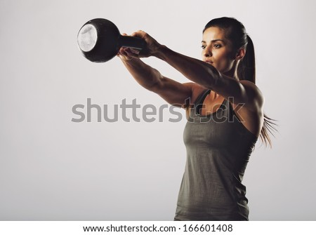 Image of young attractive female doing kettle bell exercise on grey background. Fitness woman working out. Crossfit exercise. - stock photo