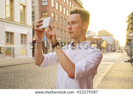 image of young attractive man take photo on mobile