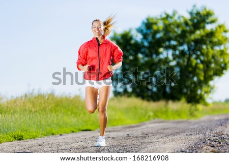 Image of young attractive woman running outdoor - stock photo