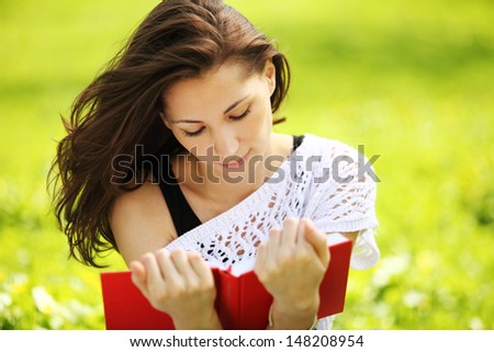 Image of young beautiful woman in summer park reading book - stock photo