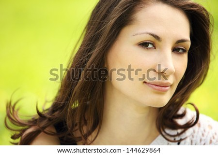 Image of young beautiful woman in summer park smiling - stock photo