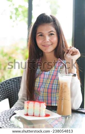 Image of young brunette in open air cafe looking at camera