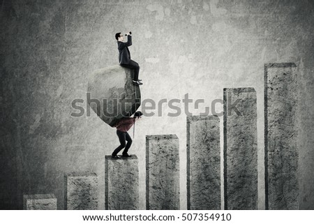 Image of young businessman climbing a business chart while carrying a big stone and his partner looking through binoculars on the stone