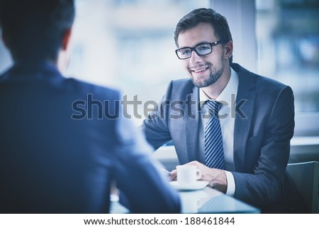 Image of young businessman having talk with his colleague - stock photo