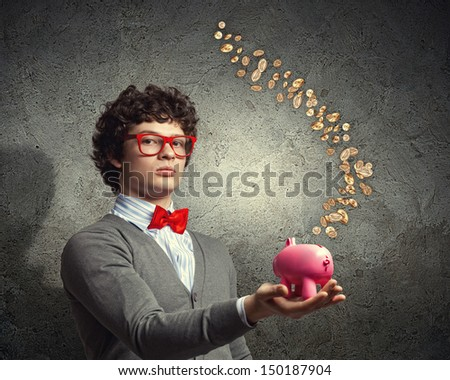 Image of young businessman in red glasses holding moneybox - stock photo