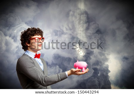 Image of young businessman in red glasses holding moneybox