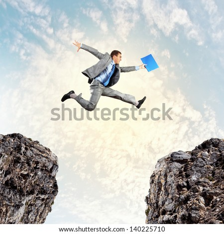 Image of young businessman jumping over gap - stock photo