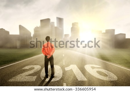 Image of young businessman looking at the city while standing on the road with numbers 2016 - stock photo