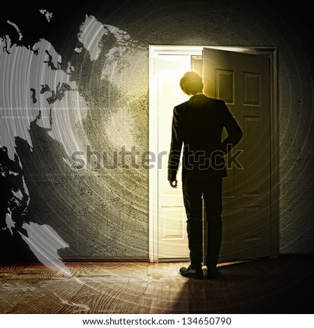 Image of young businessman opening door with lights - stock photo