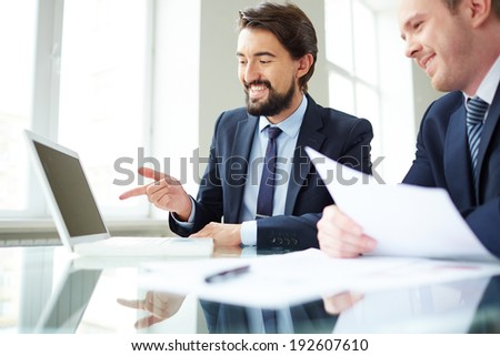 Image of young businessman pointing at laptop screen while explaining ideas to his colleague at meeting - stock photo