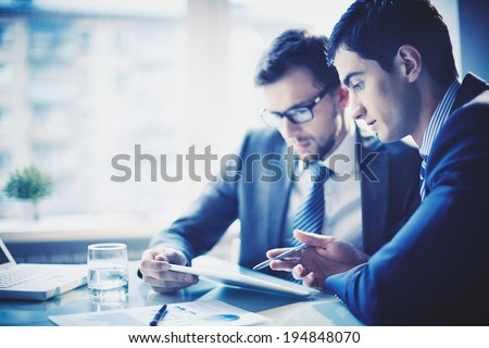 Image of young businessman pointing at touchpad while explaining his idea to colleague at meeting - stock photo