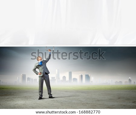 Image of young businessman pulling blank banner from above
