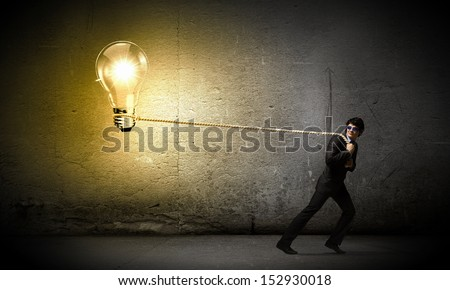 Image of young businessman pulling bulb with rope - stock photo