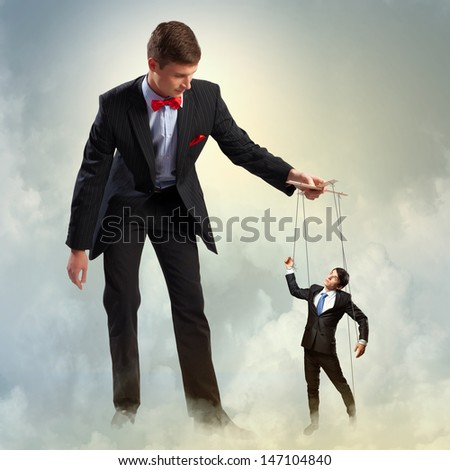 Image of young businessman puppeteer. Leadership concept - stock photo