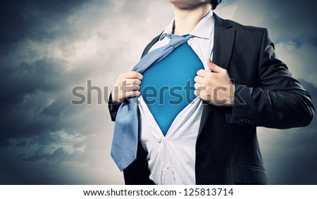 Image of young businessman showing superhero suit underneath his shirt - stock photo