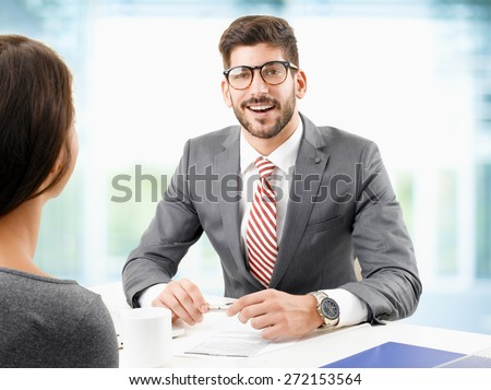 Image of young businessman sitting at desk in front of computer and doing job interview with female employee.  - stock photo