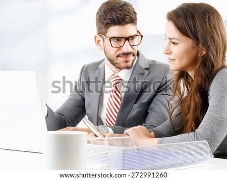 Image of young businessman sitting in front of laptop and giving advise to sales woman. Business people consulting at office. - stock photo