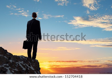 Image of young businessman standing on top of hill - stock photo
