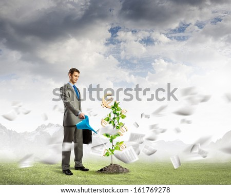 Image of young businessman watering money tree with euro symbols - stock photo