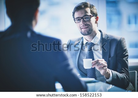 Image of young businessman with cup of coffee communicating with his colleague