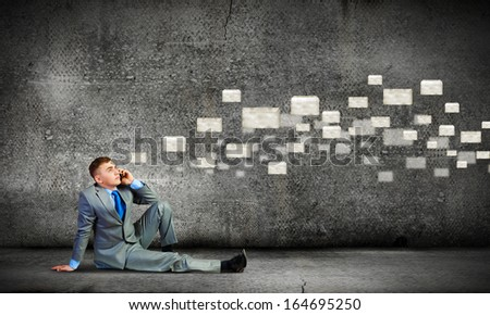 Image of young businessman with mobile phone sitting on floor - stock photo