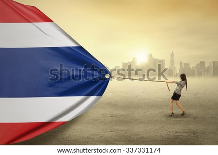 Image of young businesswoman dragging flag of Thailand with a rope, shot outdoors - stock photo