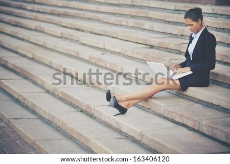 Image of young businesswoman in suit networking on steps of building - stock photo
