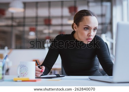 Image of young businesswoman looking at laptop while working at her desk. Female web designer taking notes from internet. - stock photo