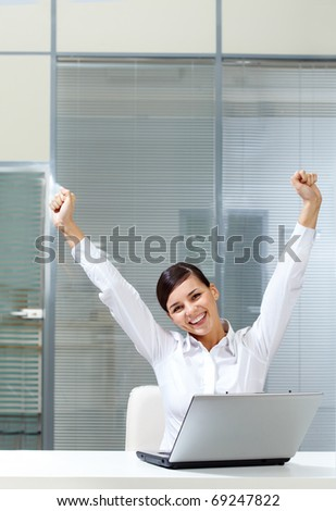 Image of young businesswoman raised arms at workplace - stock photo