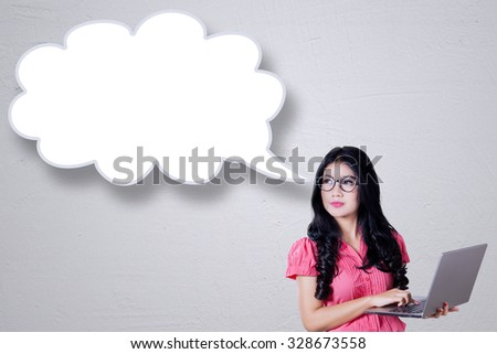 Image of young businesswoman using laptop computer while looking at empty speech bubble - stock photo
