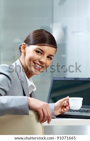 Image of young businesswoman with cup at workplace in office