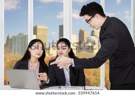 Image of young caucasian businessman talking with two multi ethnic businesswomen in the office - stock photo