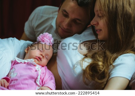 Image of young caucasian family indoor. Father, mother and cute little girl. Dad, mum and newborn baby in pink suit. - stock photo