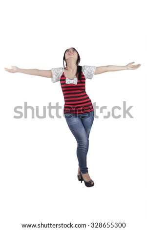 Image of young chinese girl enjoying freedom with outstretched arms in the studio - stock photo