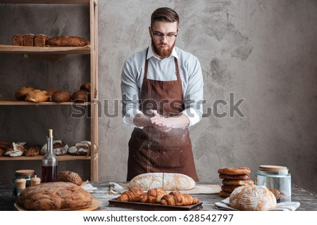 Image of young concentrated bearded man wearing glasses baker cut the bread.