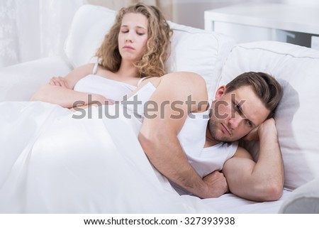 Image of young couple arguing in bed - stock photo