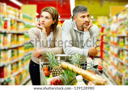 Image of young couple with cart in supermarket - stock photo