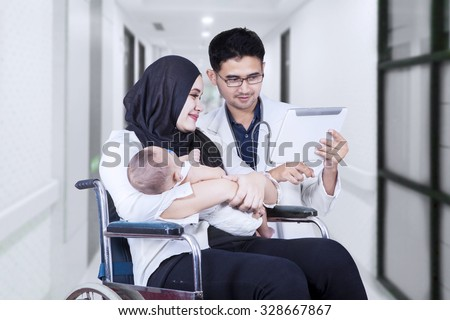 Image of young doctor showing digital tablet on the disabled woman sitting on the wheelchair with her baby