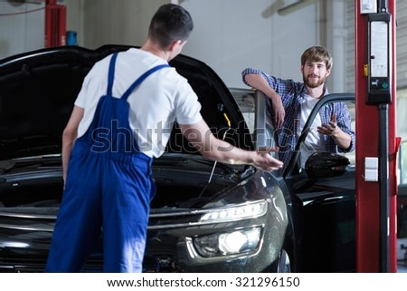 Image of young driver and auto service worker diagnosing car - stock photo