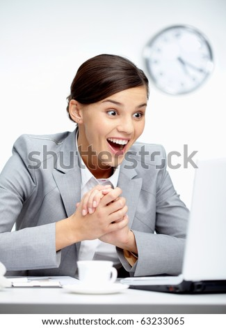 Image of young employer looking at laptop with glad expression in office - stock photo