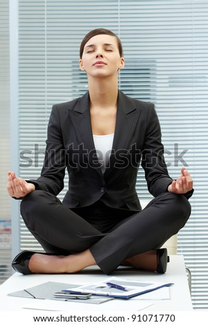 Image of young employer on workplace and meditating - stock photo